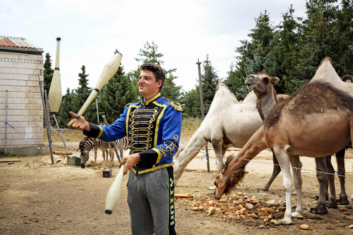Adrian Schmidt jongliert in Paradeuniform vor der Futterstelle der Kamele und Dromedare. Dahinter befindet sich die Freiluft-Manege, wohin die Aeros-Zirkusleute zur öffentlichen Probe einladen.