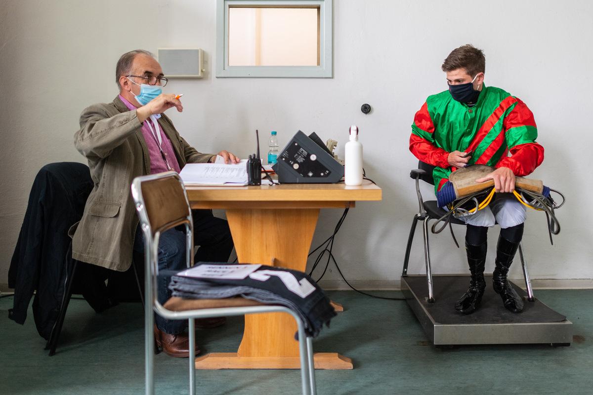 Wiegen mit Mund-Nasen-Schutz: Klaus Kunath kontrolliert das Gewicht von Jockey Lukas Delozier. Das wird für jedes Rennen extra festgelegt. Der Unterschied wird unter anderem durch Bleigewichte ausgeglichen.