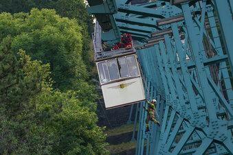 Feuerwehrleute hängen an Schwebebahn