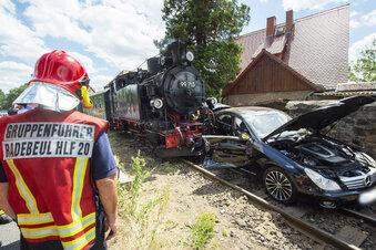 Schmalspurbahn schleift in Radebeul Auto mit
