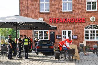 Auto rast auf Restaurant-Terrasse