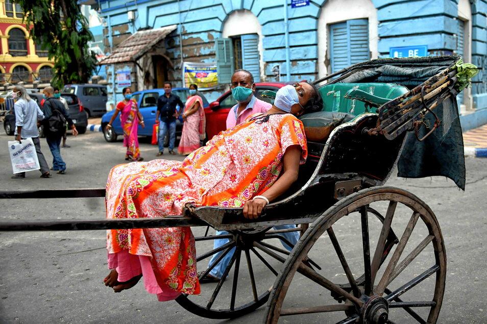 Eine an Covid-19 erkrankte Frau wird auf einer Rikscha zum Kolkata Medical College Hospital in Kolkata gebracht. Der Gründer einer Hilfsorganisation gab nun mehr als einem Dutzend Rikscha-Fahrer Schutzanzüge, Sauerstoffflaschen, Oximeter und weitere mediz