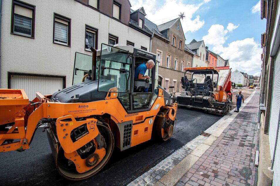 Die Andrä Straßen- und Wegebau GmbH aus Leisnig hat am Montag die Tragschicht auf die Harthaer Annenstraße aufgebracht. Foto: Dietmar Thomas