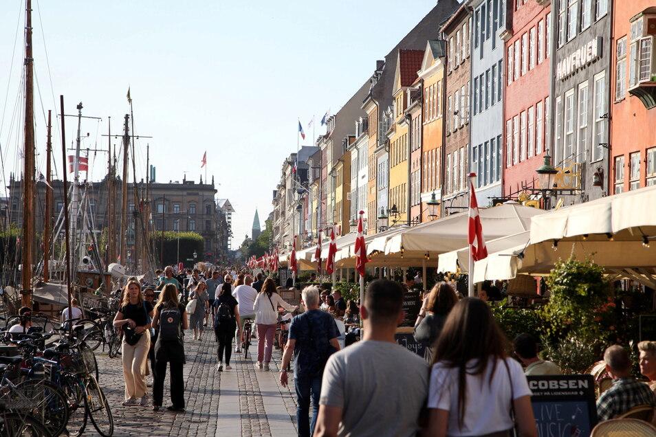 Passanten spazieren am Kopenhagener Nyhavn entlang, dem bei Touristen beliebten Hafen mit seinen bunten Häuschen.