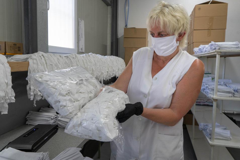 Karin Haufe, Mitarbeiterin in der Wäscherei Zierenberg, zeigt zwei der Päckchen, in denen die Mund- und Nasenmasken versandt werden. In Bischofswerda werden sie nach einem zertifizierten Verfahren gewaschen und desinfiziert.