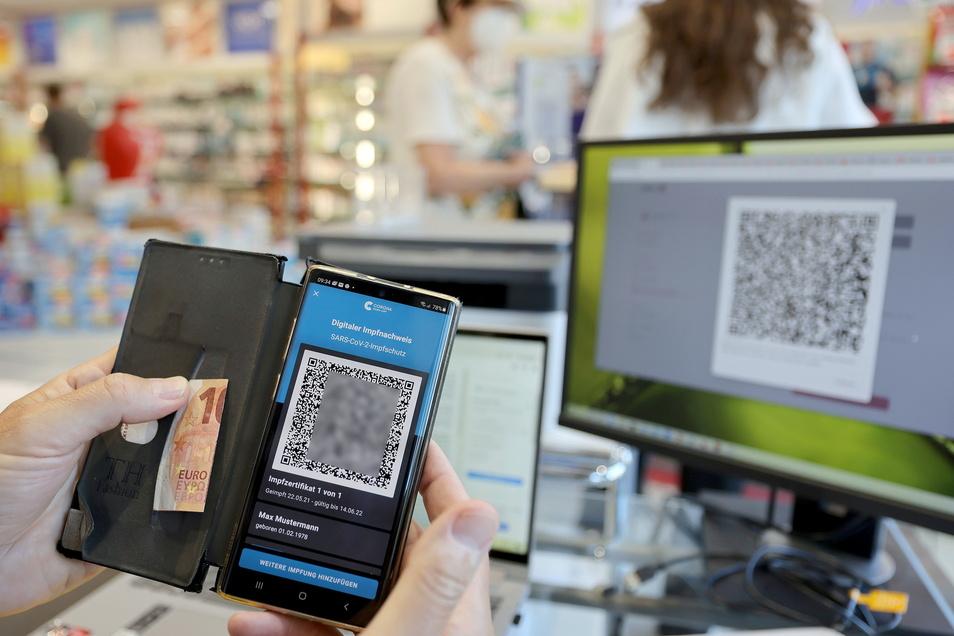 Der digitale Impfnachweis ist auf einem Smartphone in einer Kölner Apotheke zu sehen. Ein Teil der Apotheker startet mit dem Ausstellen des neuen digitalen Nachweises einer Corona-Impfung.