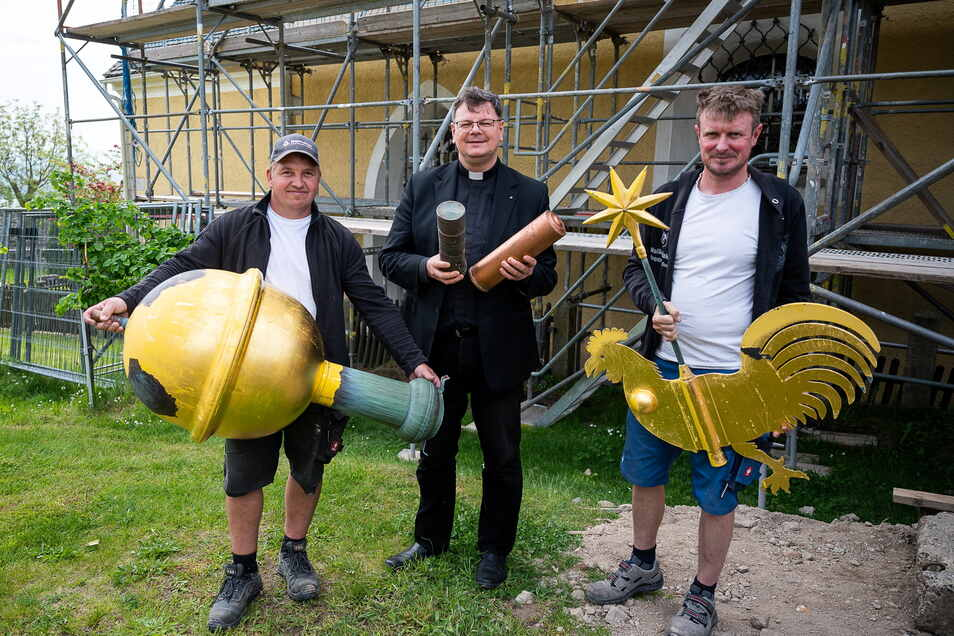 Pfarrer Roland Elsner hält die Kapseln und Mitarbeiter der Dachdeckerei die Turmkugel und den Wetterhahn.