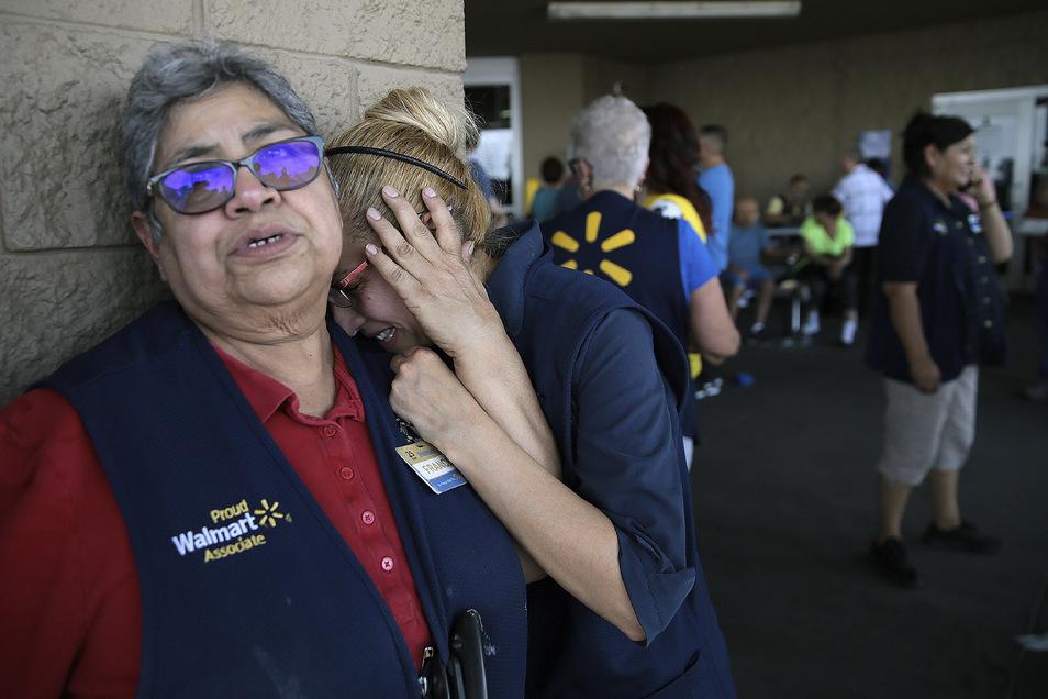 Mitarbeiter von Walmart stehen erschüttert vor der Tür des Ladenkomplexes, in dem ein Mann zahlreiche Menschen erschossen hat.