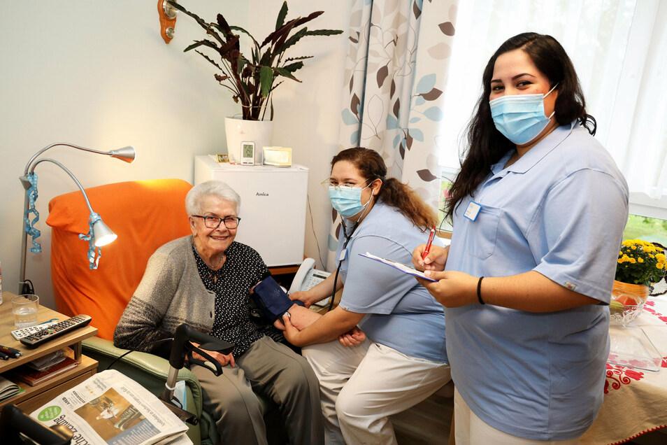 Melissa Aguilera (rechts) und Ivette Velázquez (Mitte) kümmern sich gern um Heimbewohnerin Erika Sacher.