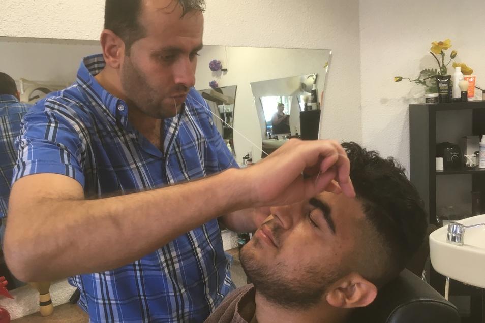 Mit der traditionellen Fadentechnik entfernt der syrische Friseur Waseem störende Haare im Gesicht.