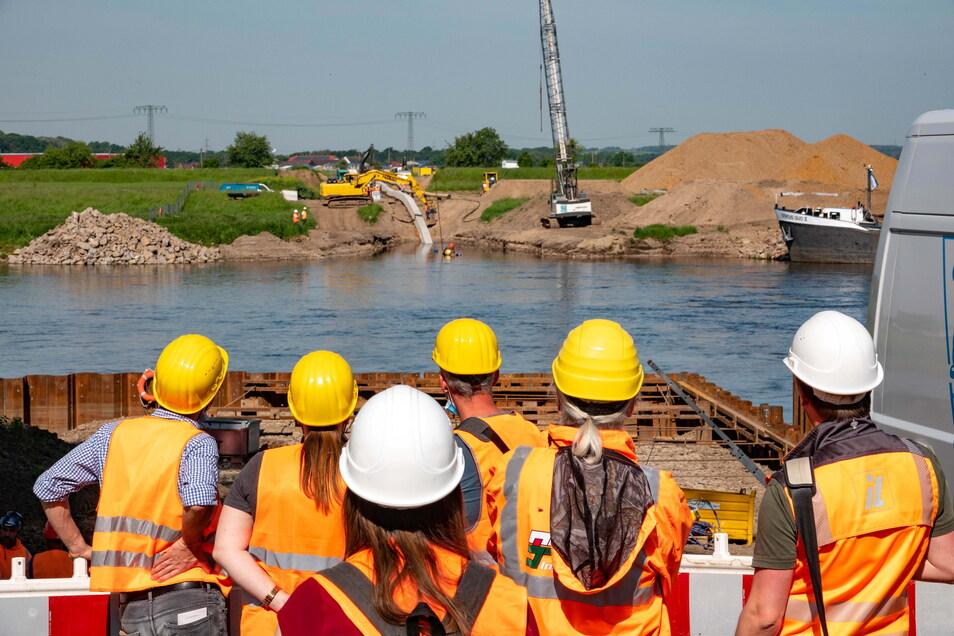 Gespannt: Zahlreiche Mitarbeiter beobachten, wie der Düker ins Wasser gleitet. Insgesamt sind 50 Leute vor Ort - von Firmen und Behörden.