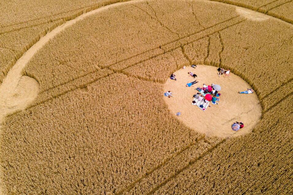 Menschen laufen durch einen Kornkreis in einem Weizenfeld.