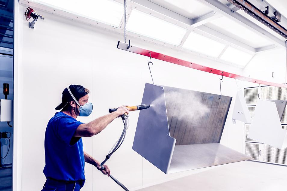 Stefan Weser beschichtet ein Bauteil per Hand. Die dabei entstehenden Partikel werden durch die Düsen im Hintergrund abgesaugt.