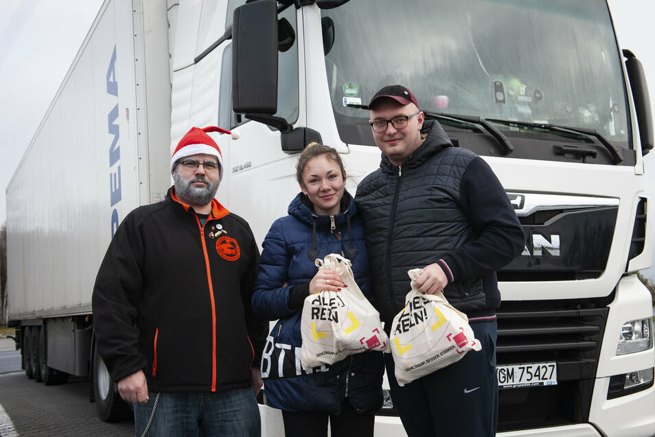 Trucker-Weihnachtsmann Enrico Poethig (l.) mit dem ukrainisch-polnischen Fernfahrerpaar Nazar und Hana Bachuk auf dem Schönfelder Autohof.
