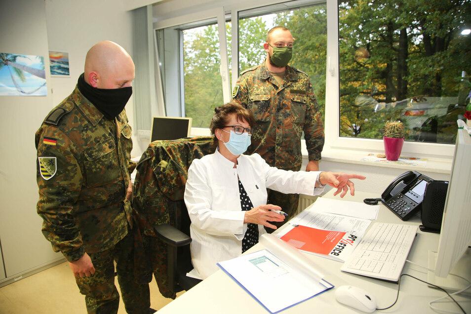 Dr. Annelie Jordan, Abteilungsleiterin des Gesundheitsamtes Mittelsachsen (Mitte), erklärt Stabsunteroffizier Marcus Patzeck (links) und Stabsunteroffizier Benjamin Weinschenk die Aufgaben bei der Kontaktverfolgung.