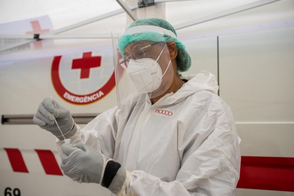 Eine Mitarbeiterin des Gesundheitspersonals bearbeitet einen Corona-Test am Platz da Parada in LIssabon.