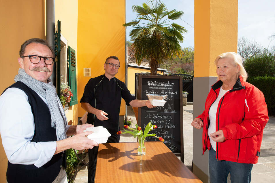 Dirk Hesse (llnks) von der Einkehr am Palmenhaus in Pillnitz ist froh, dass sein Abholangebot gut angenommen wird. Küchenchef Uwe Gnewuch hat für Kundin Ingrid Klengel schon alles zusammengepackt.