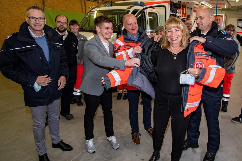 Viele Männerhände helfen Petra Köpping in eine Jacke der Johanniter, die die Leisniger Truppe mit dem Namen der Gesundheitsministerin versehen hat.