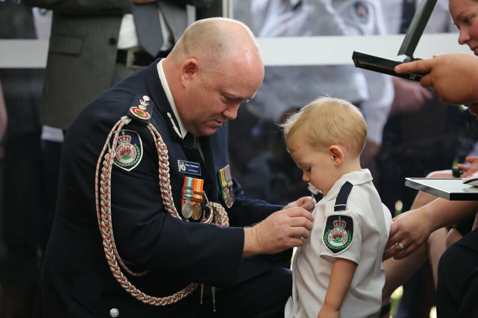 Kommissar Shane Fitzsimmons (l) überreicht dem Sohn des freiwilligen Feuerwehrmannes Geoffrey Keaton bei dessen Beerdigung stellvertretend eine posthume Auszeichnung für seinen mutigen Einsatz.