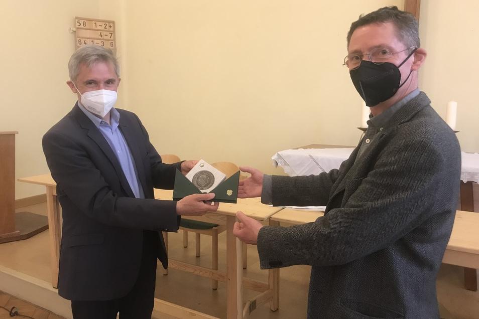 Holger Böhme (rechts) bekommt die Medaille mit der Bitte übergeben, irgendetwas für die Sächsische Verfassung zu tun.