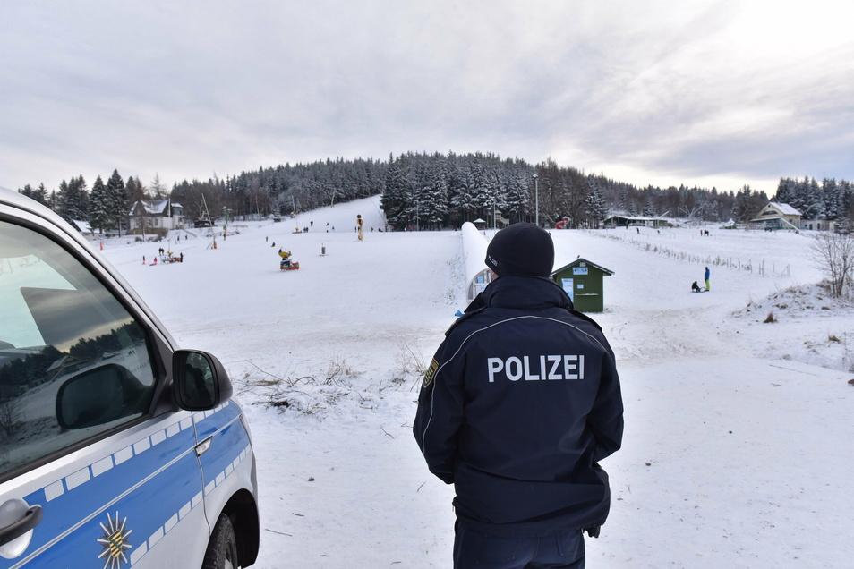Polizist am Skihang in Altenberg. Die Gäste hatten Kennzeichen wie DD, BZ und MEI.