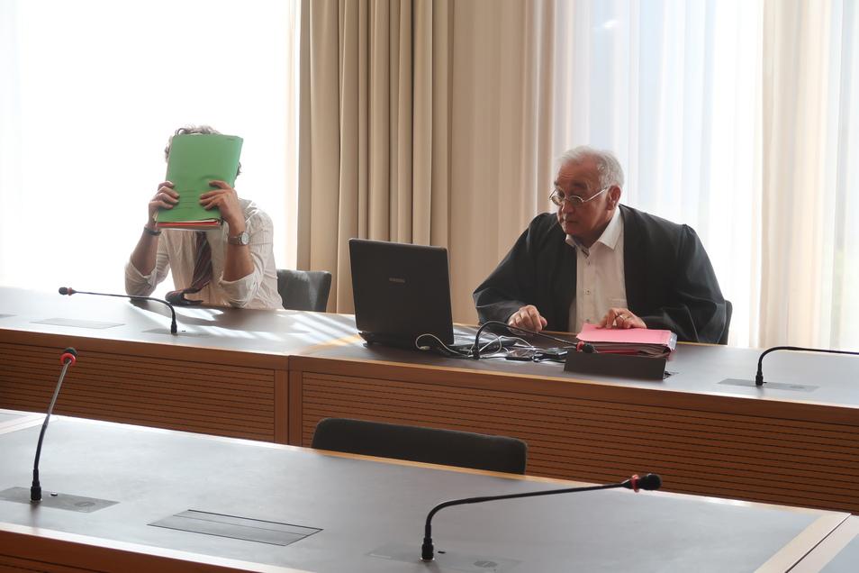 Weißes Hemd, Krawatte, das Gesicht hinter einer Akte versteckt - so saß Gerd E. am Mittwoch im Landgericht Dresden. Neben ihm sein Verteidiger Michael Flintrop.