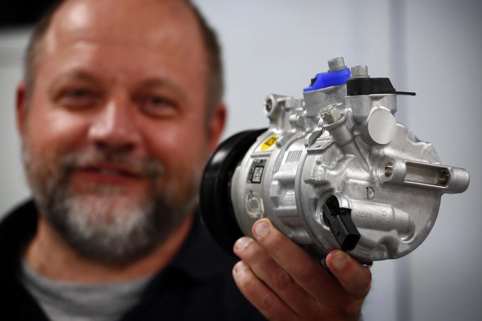 Vizepräsident Ronald Juhnke zeigt einen Klimakompressor. Er ist das Herzstück der Kllimaanlage eines Autos und kann in Straßgräbchen jetzt wieder vom Band laufen.