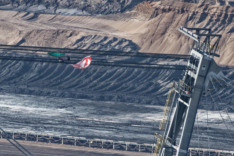 Eine Fahne und Ausrüstungsgegenstände hängen in den Seilen eines Absetzers im Braunkohletagebau Garzweiler II. Klimaaktivisten haben einen Bagger und einen Absetzer besetzt.