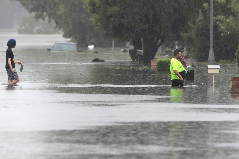 Ein Mann und eine Frau gehen in Windsor über eine überflutete Straße. Tagelanger Starkregen hat im Südosten Australiens zu einem katastrophalen Hochwasser und der Evakuierung ganzer Ortschaften geführt.