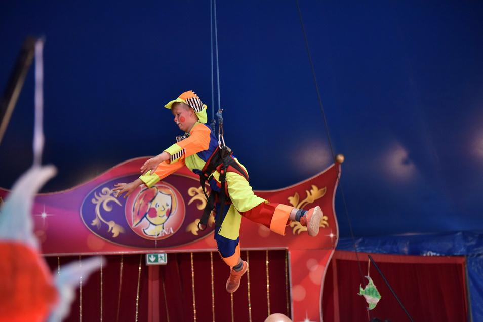 Der Viertklässler Clown Janik schwebt über den anderen Kindern in der Manege.