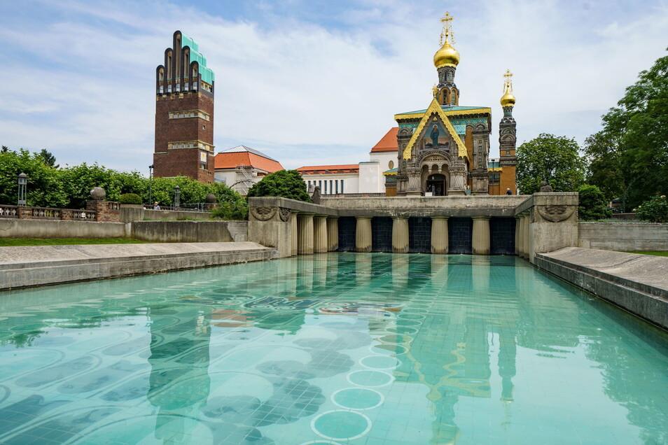 Der Hochzeitsturm (l.), das Ausstellungsgebäude (M) und die russische Kapelle (r.) spiegeln sich auf der Mathildenhöhe im Lilienbecken