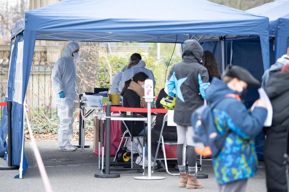 Medizinisches Personal und Besucher stehen auf einem Parkplatz vor dem Zoo. Der Tierpark bietet an den Wochenenden kostenlose Corona-Schnelltests für seine Besucher an.
