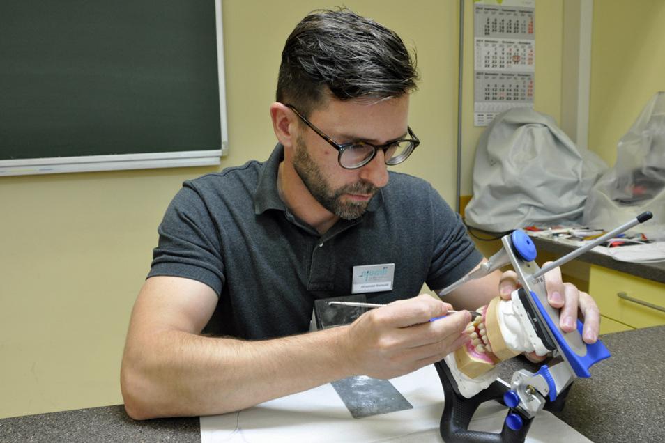 Zahntechnikermeister Alexander Meiwald demonstriert die Aufstellung einer Totalprothese.