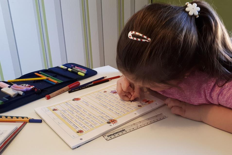 Karlotta aus der 2. Klasse beim Heimunterricht in ihrem Kinderzimmer. Sie gibt sich große Mühe, dass auch alles schön aussieht.