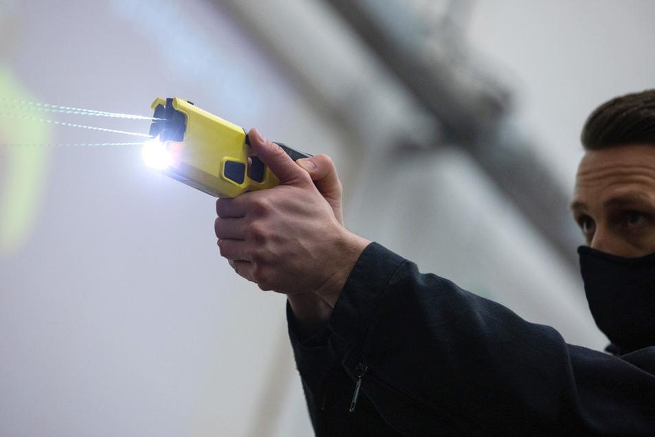 Ein Polizeibeamter demonstriert einen Schuss mit einem Distanzelektroimpulsgerät (DEIG oder auch Taser).