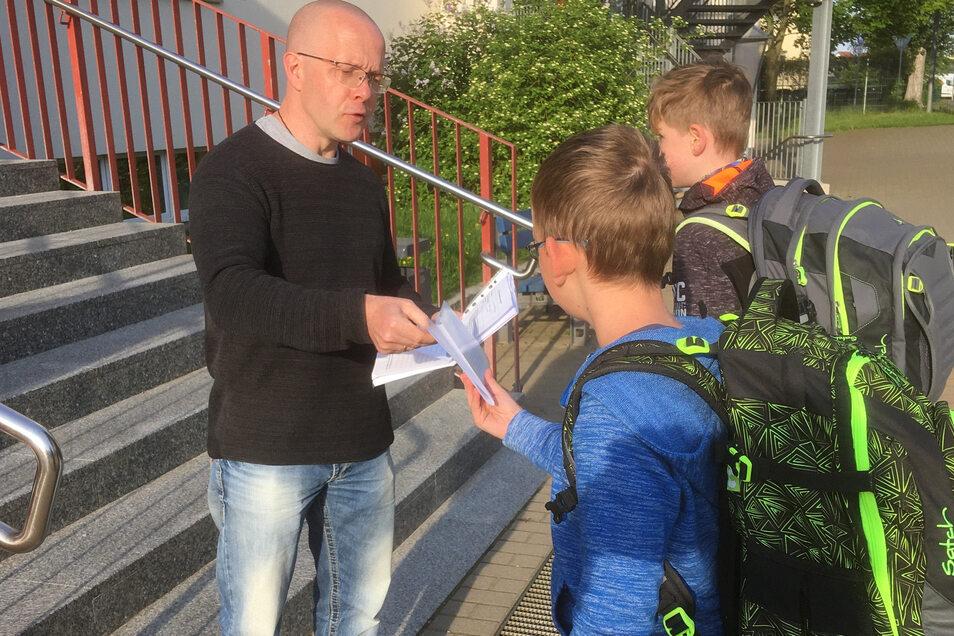 An der Großenhainer Grundschule Am Schacht nimmt Lehrer Mario Janta die Gesundheitserklärung der Schüler entgegen.