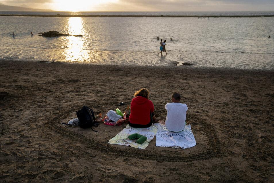 Menschen verfolgen am Strand den Sonnenuntergang auf der spanischen Insel Gran Canaria. Deutschland hat nun auch die Kanaren zum Risikogebiet erklärt.