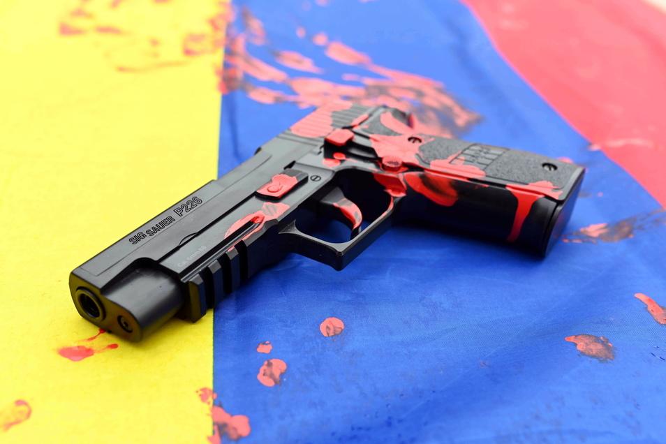 """Karlsruhe: Bei einer Protestaktion gegen den Waffenhersteller Sig Sauer liegt auf einer kolumbianischen Fahne eine untauglich gemachte Softairwaffe auf der """"·Sig Sauer P226"""" steht und die mit roter Farbe bekleckert ist."""