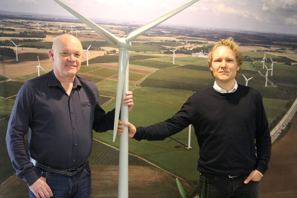 Die beiden Geschäftsführer Frank Bündig (links) und Matthias Bleil stehen vor einer Aufnahme eines Windenergieparks, für den die Firma Energieanlagen Frank Bündig das Projekt erstellt hat.