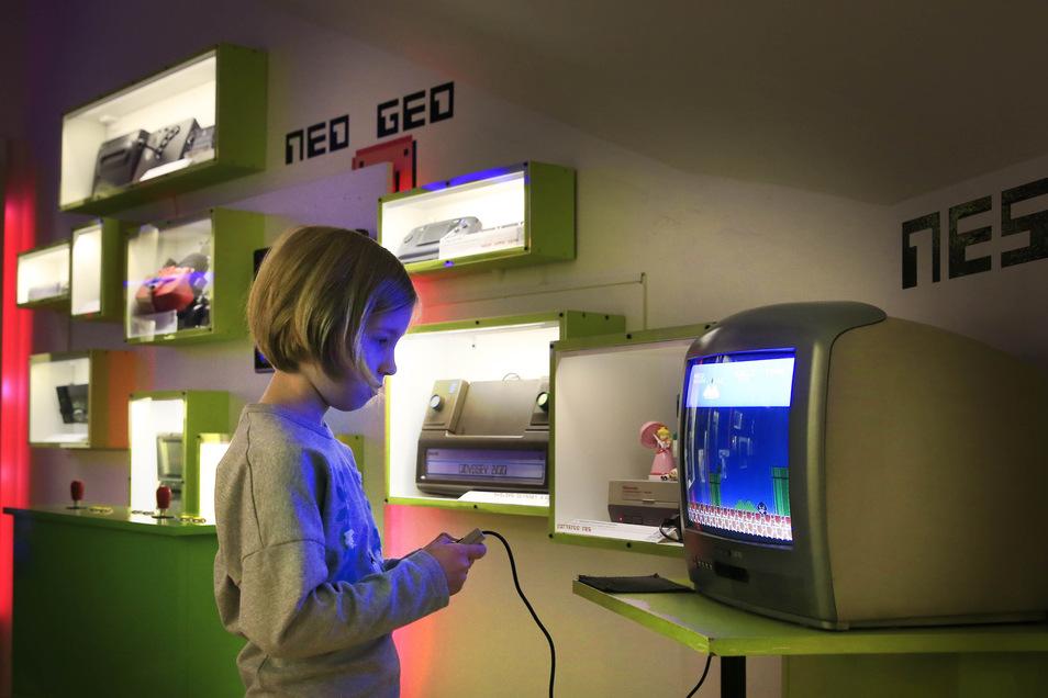 Im Obergeschoss des Hauses sind alte Konsolen- und Videospiele ausgestellt (kl. Bild). Gäste können damit spielen. Hier aber probiert Maja, Tochter der Museumsbesitzer, ein Spiel aus.