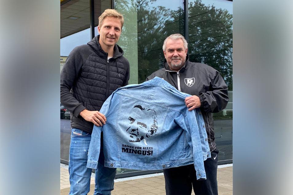 Marco Hartmann (l.) und Maik Hebenstreit von den Sportfreunden 01 Dresden Nord zeigen die Minge-Jeansjacke, die für den guten Zweck versteigert wird.