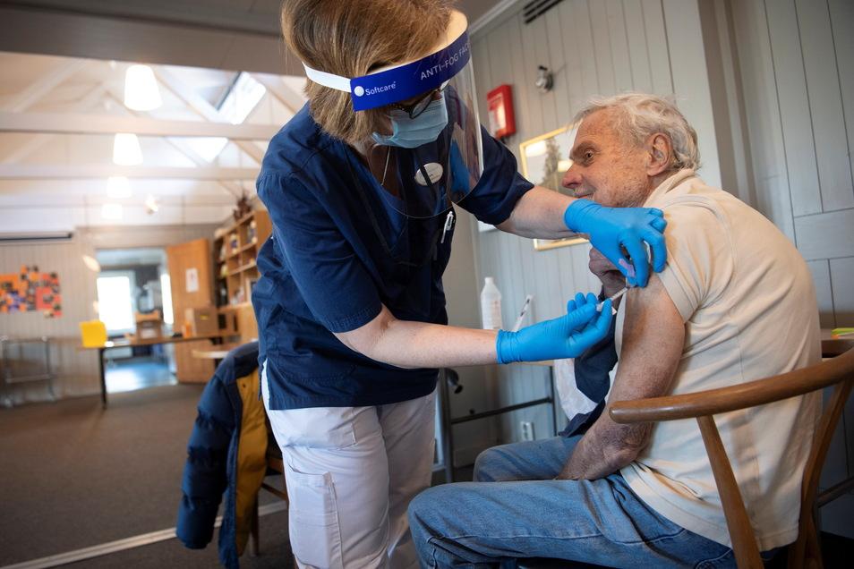 Eine Gesundheitsarbeiterin verabreicht einem Mann den Impfstoff COVID-19 von Biontech/Pfizer in einer provisorischen Impfklinik in einer Kirche in Sollentuna, nördlich von Stockholm.