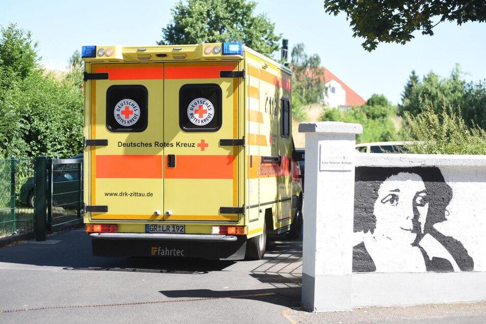 Ein Krankenwagen fährt am Donnerstagnachmittag zur Schule in Zittau. Dort ging es Kindern nach dem Mittagessen schlecht.