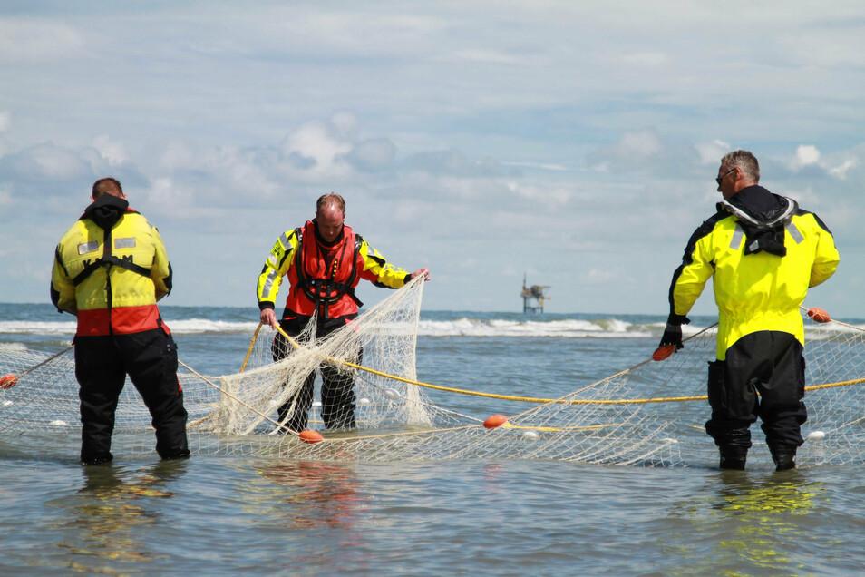 Rettungskräfte suchen mit Netzen auf der Wattenmeerinsel Ameland nach einem vermissten deutschen Mädchen. Inzwischen wurde die Suche nach der 14-Jährigen eingestellt.