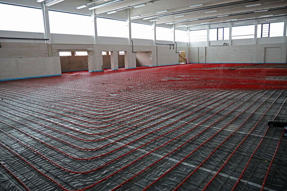 Die neue Turnhalle wird per Fußbodenheizung geheizt. Deren Leitungen werden noch mit insgesamt 90 Kubikmeter Estrich bedeckt.