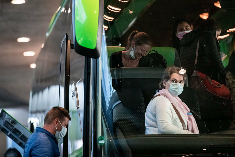 Nordrhein-Westfalen, Düsseldorf: Erntehelfer sitzen mit Mundschutzmasken in einem Bus am Ankunft-Terminal. Die Landwirte bezahlen die Flüge, die zu Sonderkonditionen angeboten werden. Die Saisonarbeiter müssen sich einem Gesundheitscheck unterziehen.