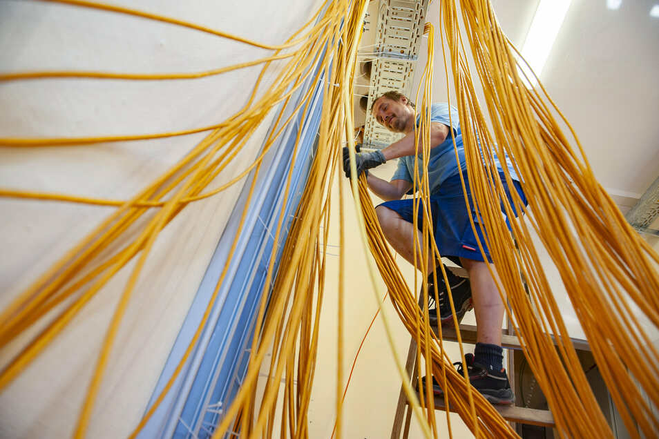 """Maik Neugebauer kämpft sich in diesen Tagen durch den """"Kabelsalat"""" in der 1. Oberschule am Kupferberg. Zu Schuljahresbeginn sollen alle Klassenräume mit digitaler Technik ausgerüstet sein."""