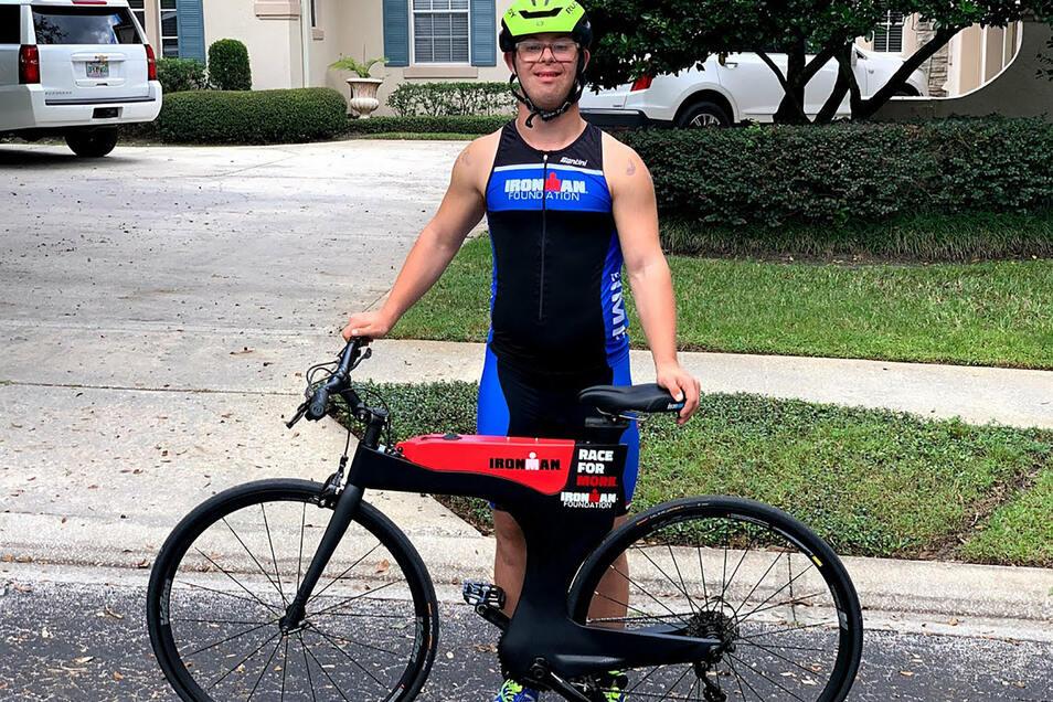 Chris Nikic steht mit Helm und Sportanzug hinter seinem Rennrad. Sport ist seine Leidenschaft.