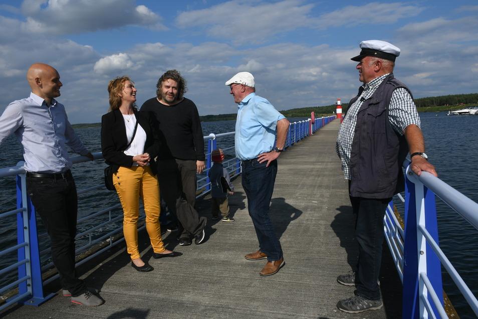 Caren Lay mit den Teilnehmern der Gesprächsrunde auf dem Wellenbrecher im Hafen von Klitten. Im Hintergrund ist der erste Leuchtturm am größten sächsischen Gewässer zu erkennen.