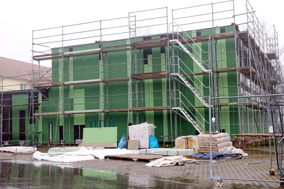Neu und schön warm: An der Sporthalle Krögis wird mit Verspätung die gedämmte Fassade angebracht.